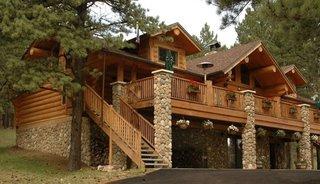 Cabana cu temelie si stalpi din piatra si balcoane din lemn