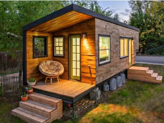 Casa mica de lemn construita din materiale reciclate