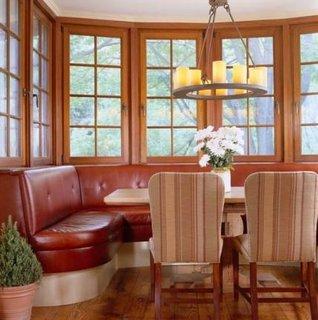 Coltar din piele maro asezat pe colt langa fereastra