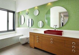 Baie moderna cu mobilier din lemn si pereti cu mozaic verde
