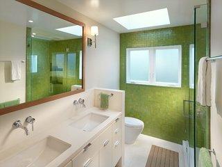 Perete placat cu faianta verde si mobilier de baie de culoare alba