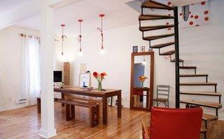 Lustre suspensii rosii in bucatarie cu masa din lemn si bancute rustice