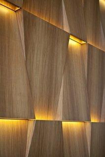 Perete imbracat in lemn cu corpuri de iluminat integrate
