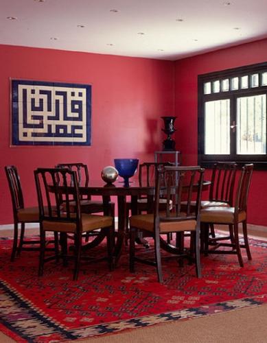 Camera pentru luat masa cu peretii rosii si chilim asortat