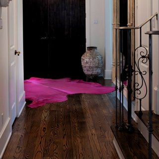Covor purpuriu asezat in hol de intrare cu parchet maro inchis