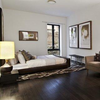 Dormitor cu parchet maro inchis si covor maro cu motive albe