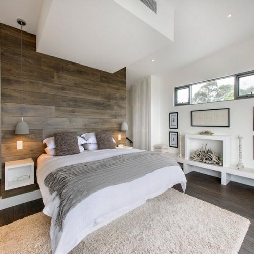 Dormitor cu perete placat cu parchet gri maro si covor shaggy crem