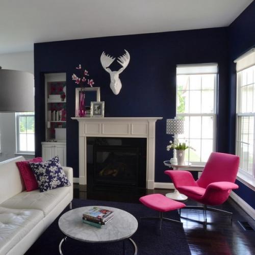 Living eclectic cu pereti si covor bleumarin si fotoliu roz aprins