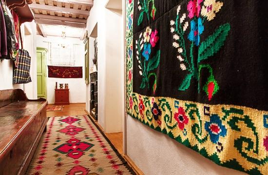 Casa traditionala cu covoare romanesti pe podea si pereti