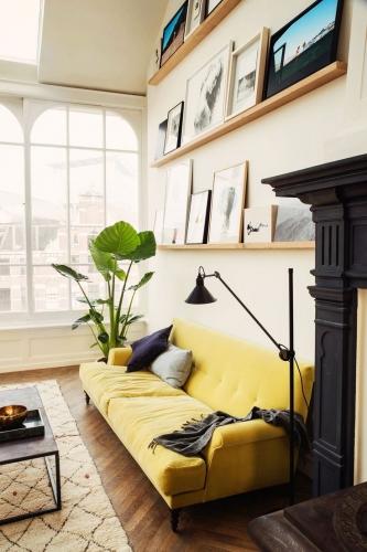 Canapea galbena pentru o pata de culoare intr-un interior incarcat de arta