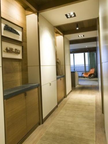 Mobilier pentru hol cu dulapuri inalte albe si comode din lemn natur