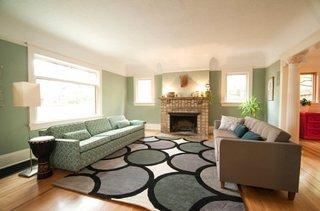 Living cu canapea verde si canapea maro asortate cu peretii si covorul