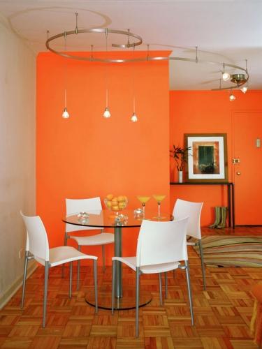Dinning zugravit cu portocaliu citric si masa rotunda din sticla si scaune albe