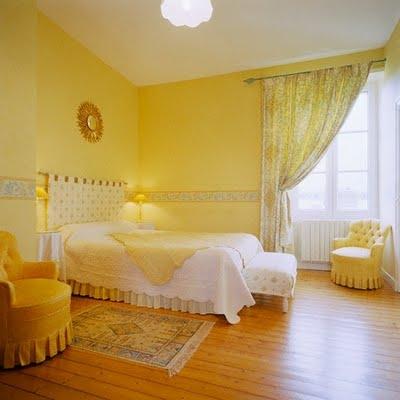 Dormitor romantic galben cu pat alb pe mijloc
