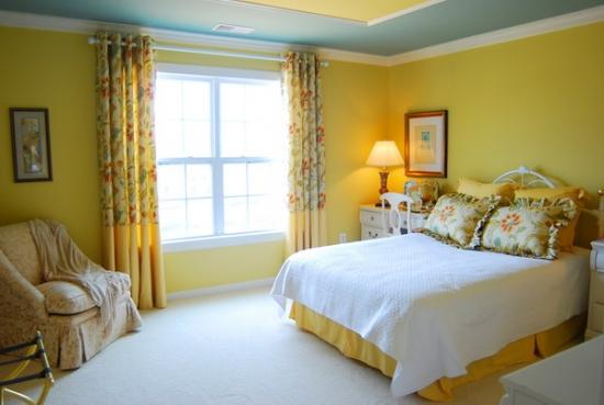 Dormitor zugravit cu galben pal si draperii cu model floral