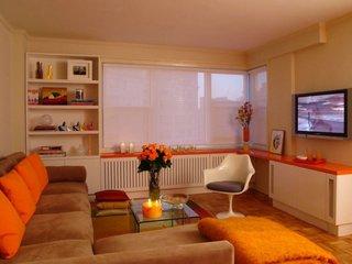 Living de apartament zugravit in crem si mobia alba cu portocaliu