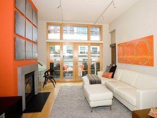 Living ingust amenajat cu canapea din piele crem, perete portocaliu si covor si tablouri gri