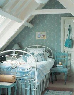 Dormitor la mansarda cu pat de o persoana din fier vopsit in alb si tapet albastru deschis