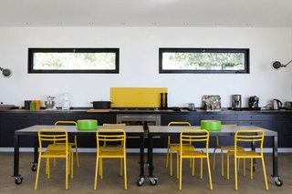 Bucatarie cu mobila si masa negre si scaune galbene