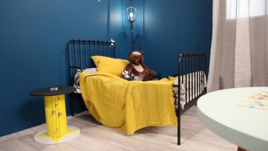 Dormitor albastru cu pat cu lenjerie galbena