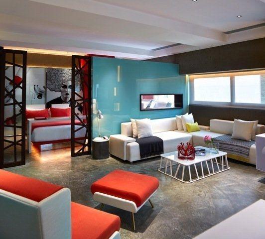 Living decorat simplu cu coltar crem si canapea de doua locuri portocaliu cu crem