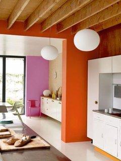 Bucatarie cu mobila alba si pereti portocalii cu roz