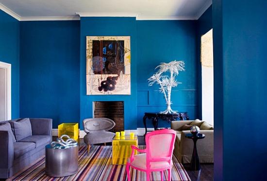 Living cu pereti albastri si scaune galbene si roz