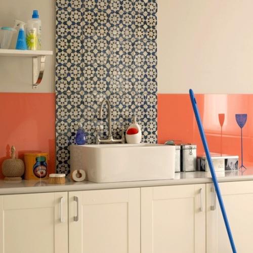 Perete in bucatarie placat cu panou portocaliu din sticla si faianta cu model