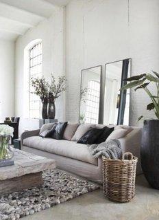 Oglinzi mari rectangulare sprijinite pe peretele din spatele canapelei