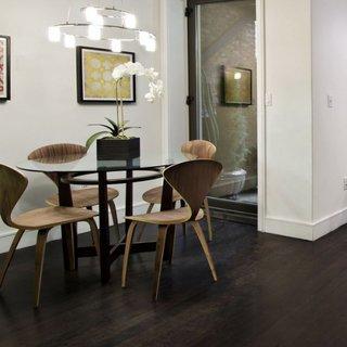 Loc pentru luat masa cu masa cu blat rotund din sticla si scaune de designer