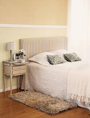 Dormitor cu tapet decorativ crem cu floricele si noptiera asortata