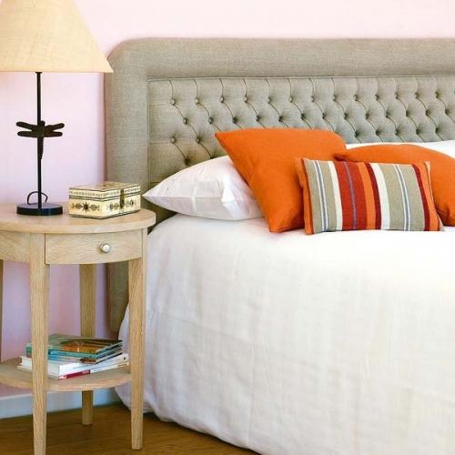 Noptiera rotunda din lemn deschis la culoare si pat cu tablie tapitata