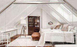 Dormitor amenajat in coltul mansardei si partitionat cu sticla
