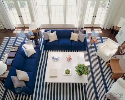 Covor mare in dungi alb albastre cu canapea albastra si fotolii albe asezate deasupra