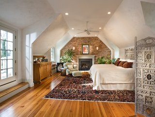 Dormitor mare cu pat matrimonial perete placat cu piatra si parchet si pervaz placate cu lemn masiv