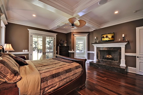 Dormitor mobilat clasic cu pereti maro inchis si parchet si mobilier din lemn masiv