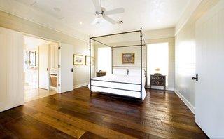Dormitor rustic cu pat simplu cu baldachin pereti albi si dusumea
