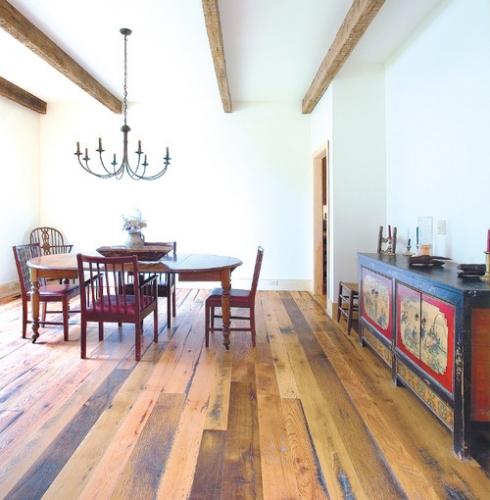 Loc pentru luat masa amenajat rustic cu dusumea din lemn si grinzi de lemn pe tavan