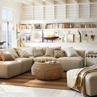 Living amenajat in alb cu crem si multe rafturi si etajere deasupra canapelei