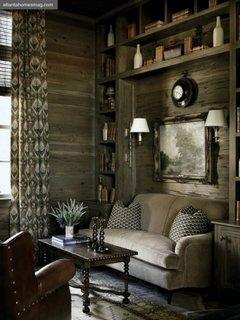 Living amenajat in stil rustic cu biblioteca pe peretele din spatele canapelei