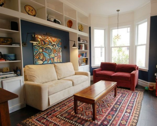 Living cu forma atipica cu peretii albastri si mobilier pe pereti alb