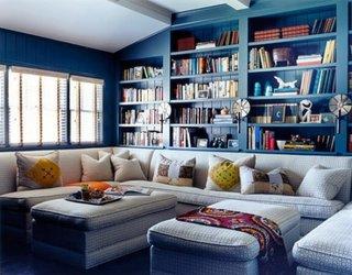 Living cu peretii cu lambriu din lemn albastru si biblioteca desupra canapelei
