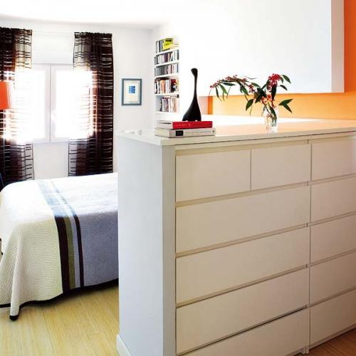 Comoda ingusta cu sertare ce desparte dormitorul de restul camerei