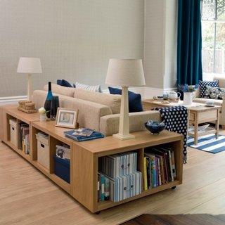 Corpuri cu etajere asezate in spatele canapelei pentru o separare vizuala a zonelor