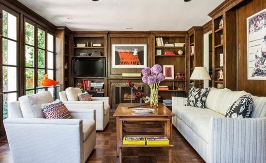 Living cu peretii placati cu lambriu din lemn si canapea si fotolii albe