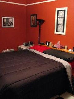 Dormitor portocaliu cu tablou tip fereastra agatat pe perete