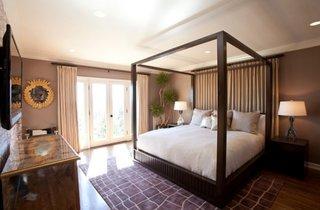 Dormitor cu pat cu cadru de lemn si baldachin si planta in ghiveci