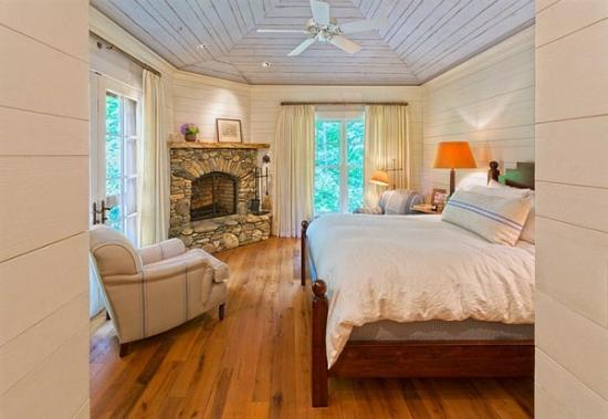 Dormitor rustic cu semineu pe colt placat cu piatra de rau