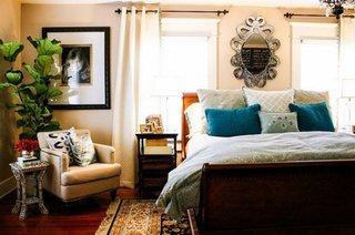 Fotoliu tapitat si masuta mica langa in dormitor cu pat pe mijloc