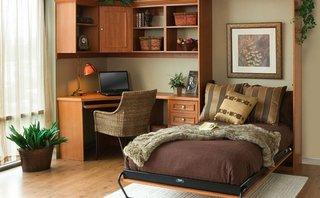 Birou pe colt cu rafturi suspendate asezat langa patul din dormitor